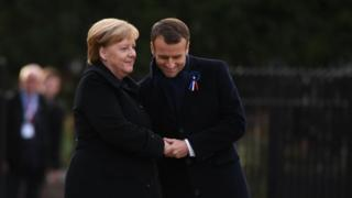 Germany's Angela Merkel and France's Emmanuel Macron embrace in the clearing of Rethondes in Compiegne