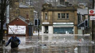 A man wades through flood waters at Hebden Bridge in West Yorkshire