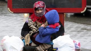 Женщина с ребенком на улице просит подаяние