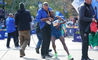 Girma Bekele Gebre of Ethiopia is helped during the Professional Men's Finish during the 2019 TCS New York City Marathon in New York on November 3, 2019.
