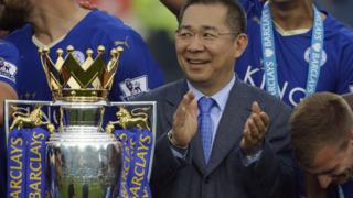 Vichai Srivaddhanaprabha applauds beside the trophy as Leicester City celebrate becoming the English Premier League soccer champions at King Power stadium