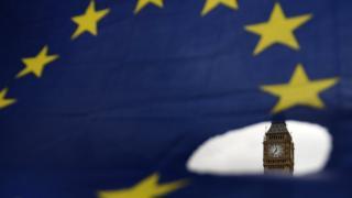 Bandeira da UE com furo mostrando o Parlamento Britânico