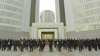Still from state TV of Turkmen exercising outside their offices