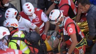 Rescue and emergency services personnel carry away a survivor on a stretcher in Amatrice (24 August 2016)