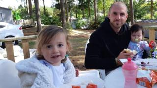Angharad Carrington-Edmunds' husband and children sitting at a table to eat