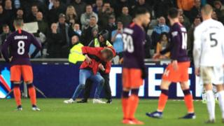 A fan is stopped on the pitch by a steward during one of the two pitch invasions