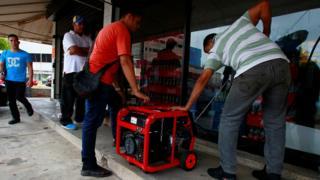 Venezolanos prueban un generador afuera de un supermercado.