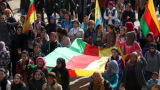 Kurdish people carry flags as they march during a protest in the city of al-Derbasiyah, on the Syrian-Turkish border, against what the protesters said were the operations launched in Turkey by government security forces against the Kurds