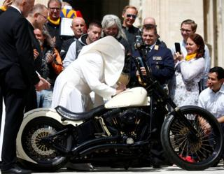 Pope Francis signs a Harley Davidson motorbike in front of a crowd of people