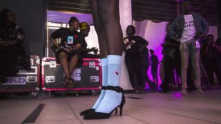 A model in socks and high heels backstage during Dakar Fashion Week in Dakar, Senegal