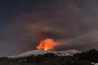 Snow-covered Mount Etna, Europe's most active volcano, spews lava during an eruption in the early hours of 16 March 2017.