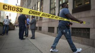 Police put up crime scene tape around the perimeter of a shooting scene outside of a federal building in the Manhattan borough of New York, on 21 August 2015.