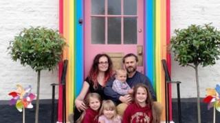 The Hemmings in front of their colourful door