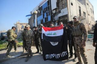 Iraqi security forces personnel hold up an Iraqi national flag over an upside-down Islamic State banner at the provincial government headquarters in Ramadi (28 December 2015)