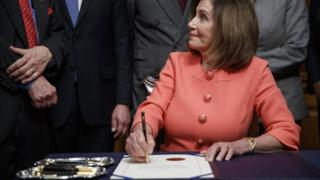Nancy Pelosi signs two articles of impeachment, with two trays of pens by her side