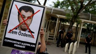 woman holding sign showing Cem Ozdemir's face with a big red X through it, security guards in the background