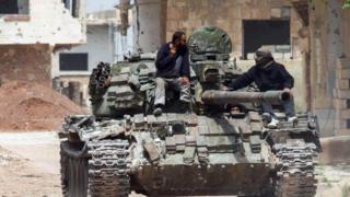 Un tanque de guerra recorriendo una calle polvorienta