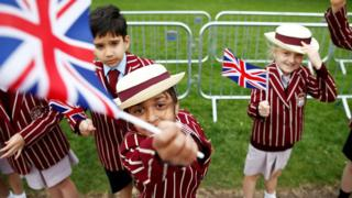School children in uniform wave Union Flags outside Windsor Castle ahead of Britain's Prince Harry and Meghan Markel's wedding, in Windsor