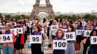 Women gathered in front of the Eiffel tower holding up numbers to represent the 101 femicides in France this year