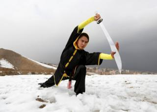 Sima Azimi, 20, a trainer at the Shaolin Wushu club, shows her Wushu skills to other students on a hilltop in Kabul, Afghanistan.