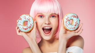 Mujer joven con dos donuts