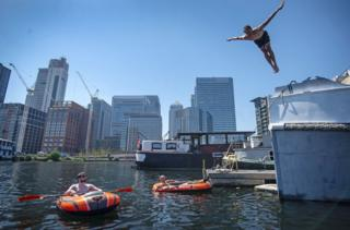 in_pictures A man dives into water in the London Docklands, as two other men in inflatable boats watch