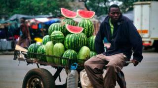 Watermelons are piled high on a cart, with few cut slices on display on top, as the seller sits on the cart's arms amid a busy marketplace