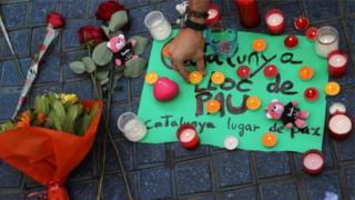 """Tưởng niệm các nạn nhân tại hiện trường, bên cạnh là tấm biển với dòng chữ: """"Catalunya, thành phố hòa bình"""""""