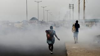 A schoolgirl walks past smoke emitted from a dump in the city of Port Harcourt.
