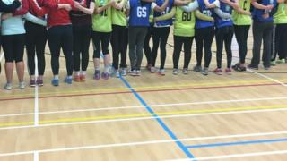 The team in a line from behind wearing netball bibs