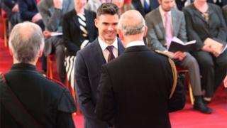 James Anderson is presented with his medal by Prince Charles at Buckingham Palace