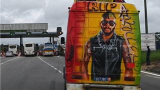 Un mini bus avec des graffitis représentant le DJ ivoirien Ange Didier Houon alias DJ Arafat sur l'autoroute près d'Abidjan.