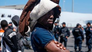 A man part group of asylum seekers, mostly from African countries, waits for a negotiation commission to walk out El Chaparral port of entry during a protest in Tijuana, Baja California state on July 9, 2019, northwestern Mexico. - Asylum seekers claimed that Mexican migration officers were selling spots on the line to get an interview with US migration authorities.