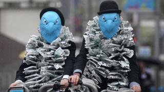 Manifestantes se fantasiam de águias em protesto contra pagamentos de executivos da instituição financeira Barclays