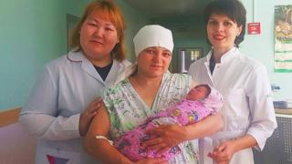 Alexandra Matrosova and her baby with doctors at the hospital