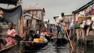 People navigate the the waterways of Makoko waterfront community in Lagos on May 15, 2018. Members of various waterfront communities and the Nigerian Slum/Informal Settlement Federation have protested on the day marking one year anniversary of the forced eviction of the Otodo Gbame community, a Lagos shanty town,