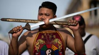 A performer gores his face with a sheath and a sword
