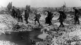 British soldiers crossing a shell-cratered, cold landscape along the River Somme