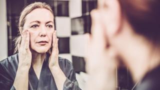 Mulher se olha no espelho