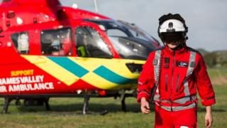 Thames Valley Air Ambulance staff member with helicopter