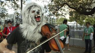 A man dressed as a wolf, playing a violin
