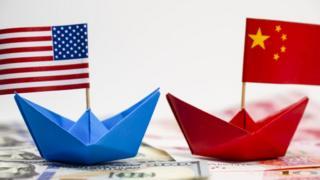 Barcos de papel con las banderas de Estados Unidos y China.