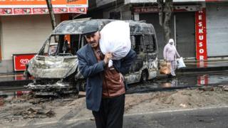 People carry their belongings as they leave their houses during clashes in central Diyarbakir on 15 March 2016.