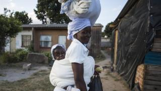 A mother carrying a bag on her head and a baby on her back - Saturday 11 May