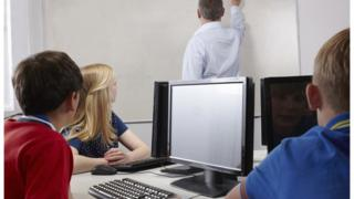 Three pupils watch a teacher while sitting at computer screens