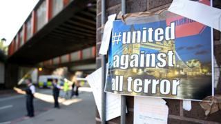 """На стене около места атаки полиция повесила плакат """"Объединимся против любого террора"""""""