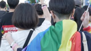 Attendees at Incheon Queer Festival draped in a rainbow flag