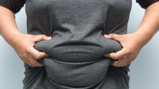 Man grabbing his belly