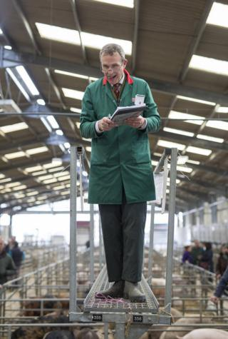 A auctioneer stands with his clipboard