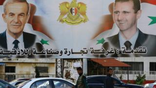 A billboard sponsored by the chamber of commerce and industry shows pictures of Syrian President Bashar al-Assad (R) and his late father former president Hafez al-Assad in the coastal city of Latakia (17 March 2016)